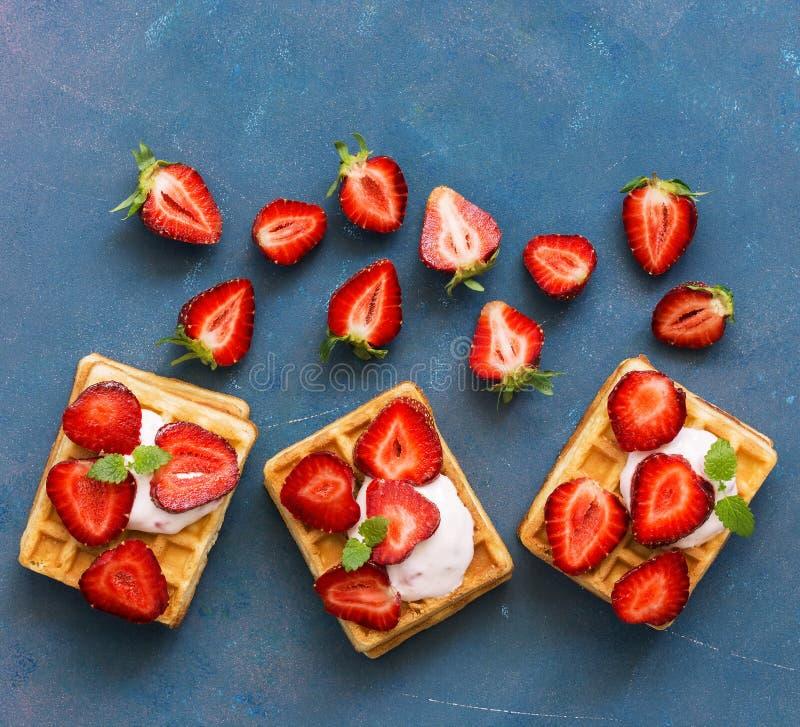 与奶油和新鲜的草莓的自创比利时华夫饼干在蓝色木质的背景 顶视图,平的位置,文本的空间 库存照片