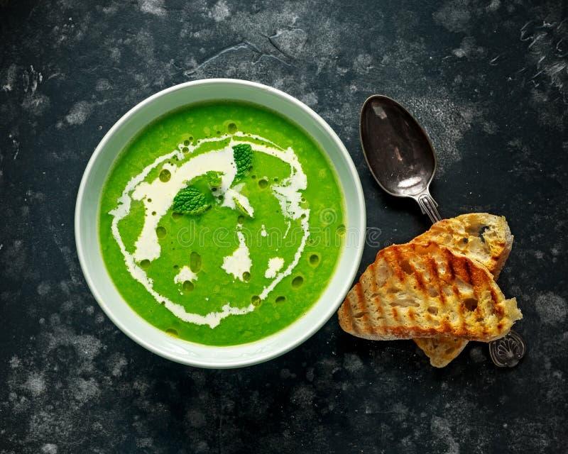 与奶油和橄榄油毛毛雨的绿色香豌豆花和薄菏汤服务用烤ciabatta多士 免版税库存照片