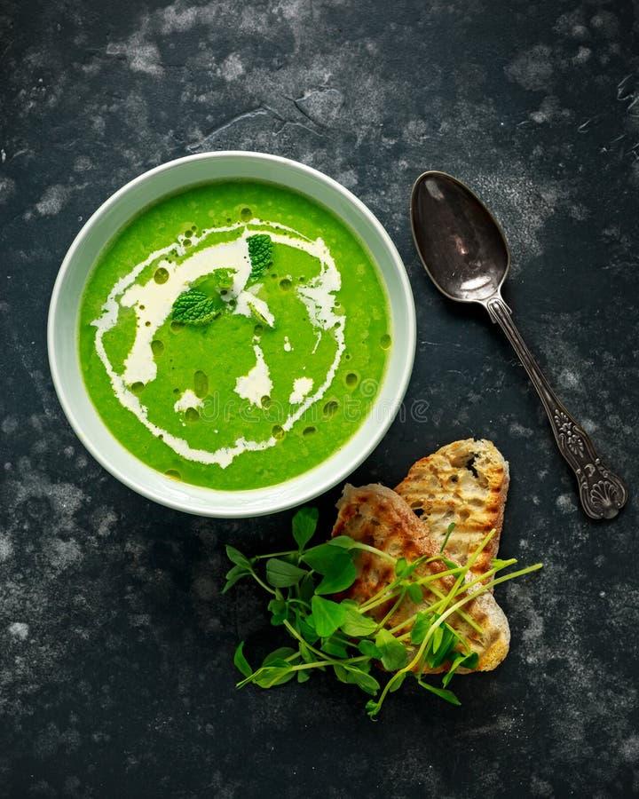 与奶油和橄榄油毛毛雨的绿色香豌豆花和薄菏汤服务用烤ciabatta多士 库存图片
