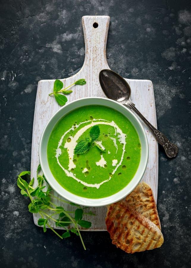 与奶油和橄榄油毛毛雨的绿色香豌豆花和薄菏汤服务用烤ciabatta多士 免版税图库摄影