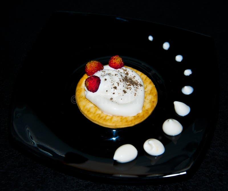 与奶油和草莓的曲奇饼在板材 免版税图库摄影