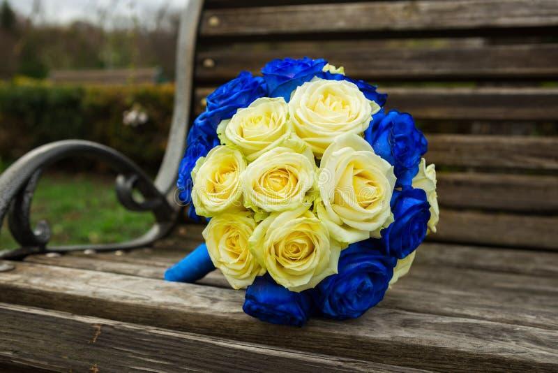 与奶油和蓝色玫瑰的明亮的婚礼花束在woode说谎 库存照片