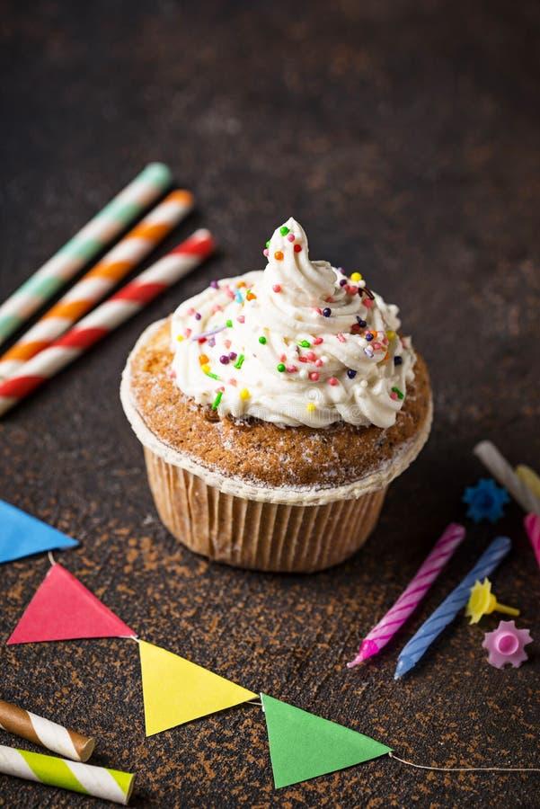 与奶油和装饰的生日杯形蛋糕 库存照片