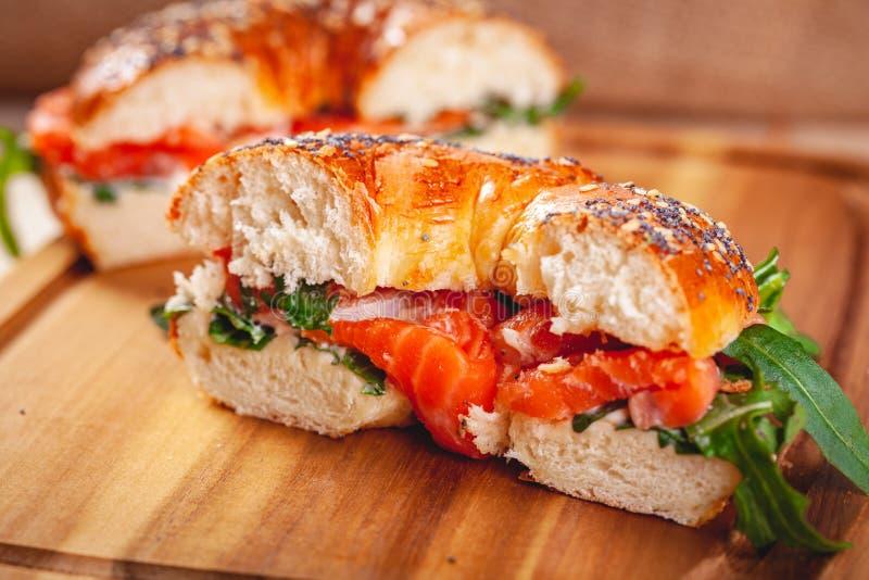 与奶油奶酪、熏制鲑鱼和芝麻菜沙拉的百吉卷在木板切成了两半 免版税库存照片