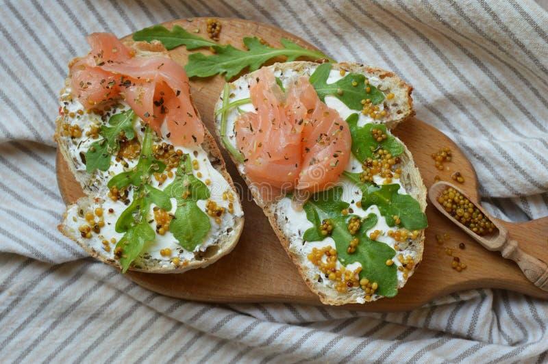 与奶油奶酪的三文鱼三明治在木板 免版税库存照片