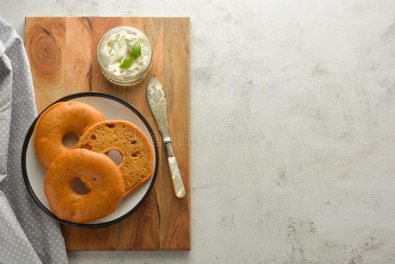 与奶油奶酪的可口百吉卷在木板,早餐顶视图的酥皮点心面包 r 库存照片
