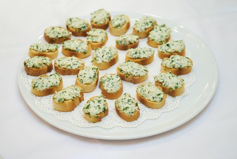 与奶油奶酪的烤面包片在白色背景的板材 免版税库存图片