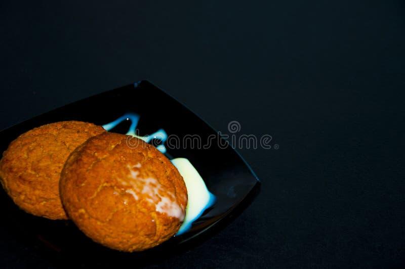 与奶油的两个曲奇饼在茶碟 免版税库存照片