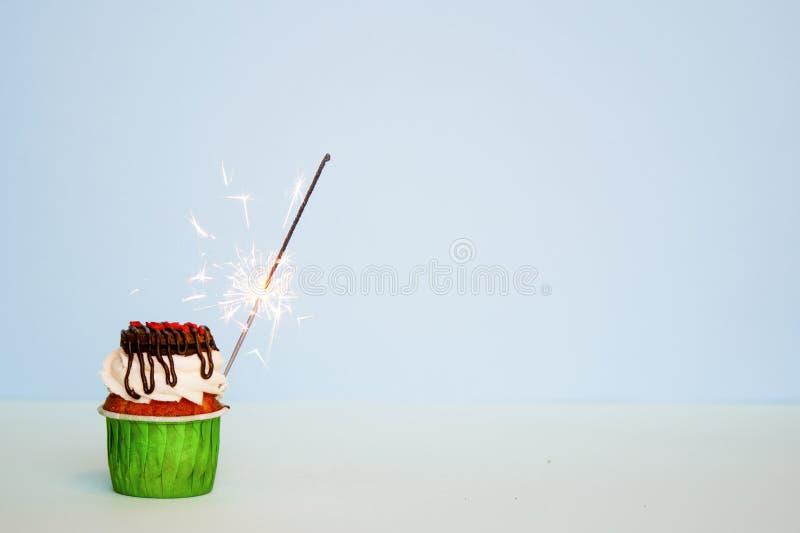 与奶油的可口,水多的与燃烧的闪烁发光物的杯形蛋糕和曲奇饼 复制空间 免版税库存图片
