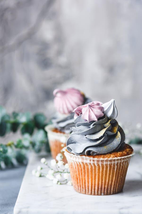 与奶油的淡色杯形蛋糕在大理石背景 免版税库存照片