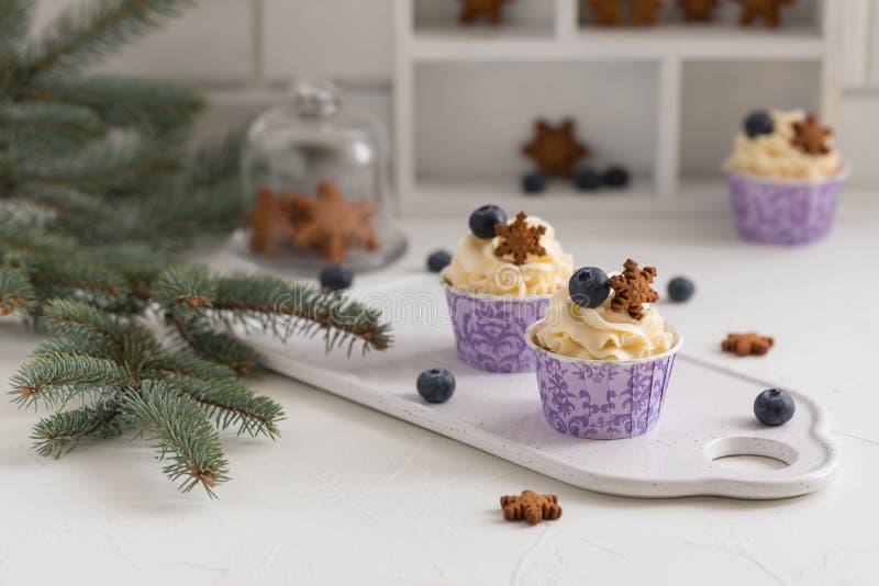 与奶油的鲜美蓝莓松饼在白色木桌,圣诞节点心上 库存照片