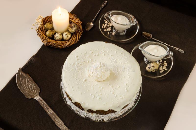 与奶油色冰的和燃烧的蜡烛的复活节蛋糕 图库摄影
