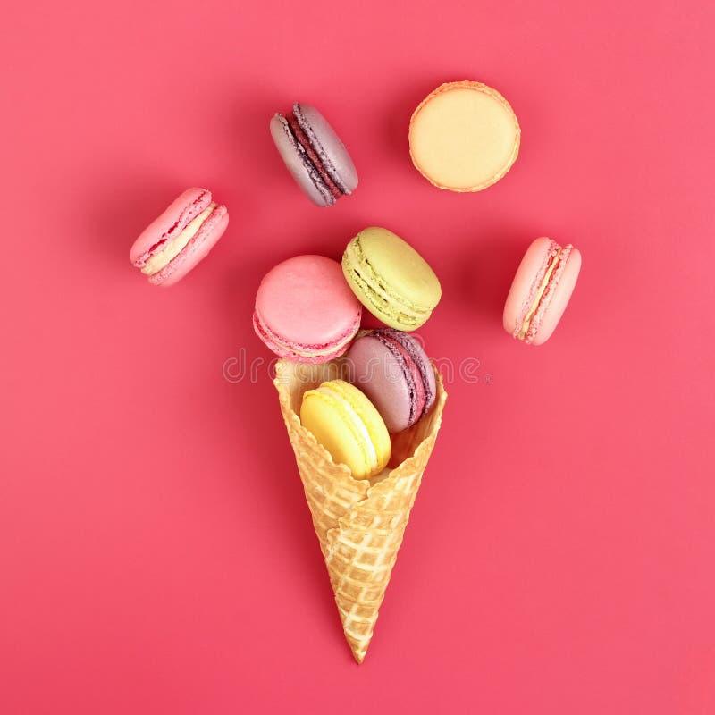 与奶蛋烘饼锥体的Macarons在桃红色背景 库存照片