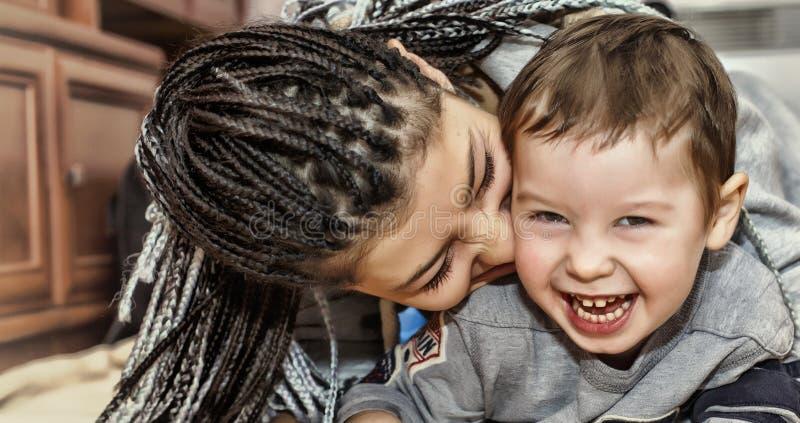 与她的儿子的深色皮肤的母亲戏剧 拉丁美洲的妈妈使用并且笑与他的小儿子 概念:愉快的母亲` s天 库存照片