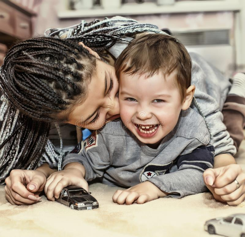 与她的儿子的深色皮肤的母亲戏剧 拉丁美洲的妈妈使用并且笑与他的小儿子 概念:愉快的母亲` s天 免版税库存照片