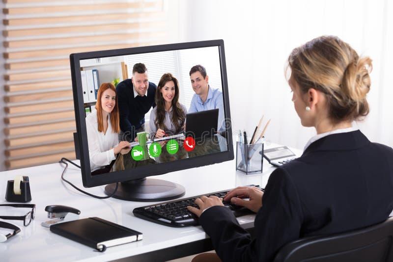 与她的同事的女实业家电视电话会议 免版税库存照片