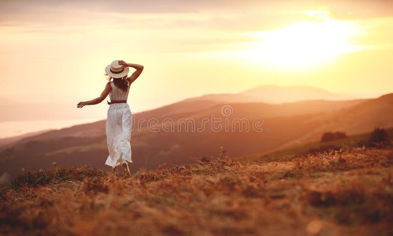 与她的后面的愉快的妇女身分在日落在自然iwith开放手上 免版税库存照片