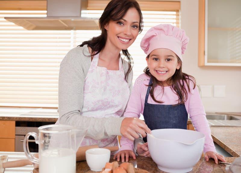 与她的女儿的母亲烘烤 免版税图库摄影