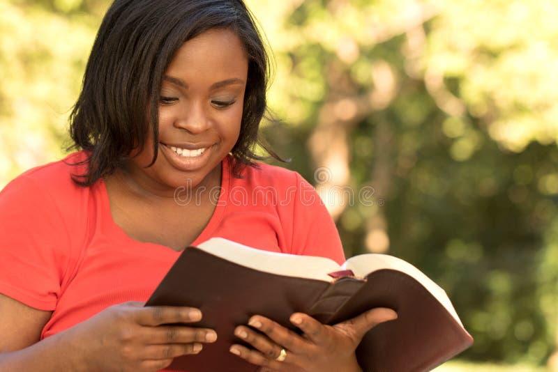 与她的女儿的母亲读书 免版税库存图片