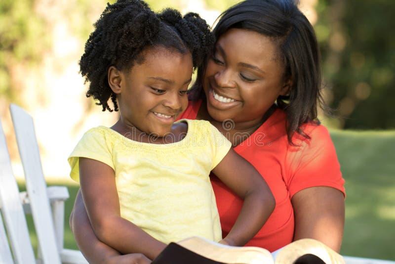 与她的女儿的母亲读书 免版税库存照片