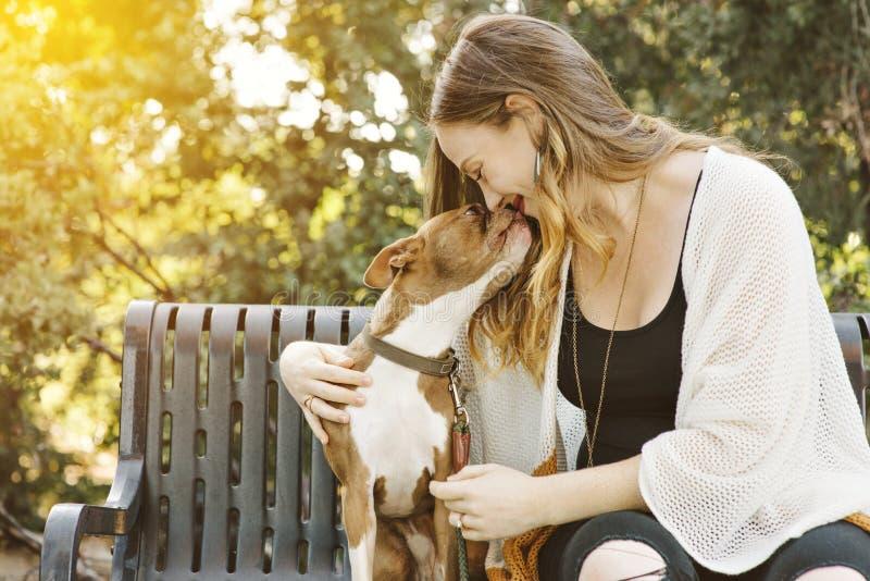 与她的小爱犬愉快的爱的关系的俏丽的白色女性千福年的污迹 免版税库存照片