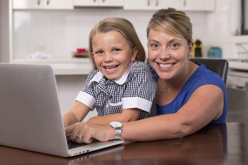 与她的年轻美好和美好的小女孩6到8岁一起的白肤金发的母亲妇女在家坐厨房享用与的 免版税图库摄影