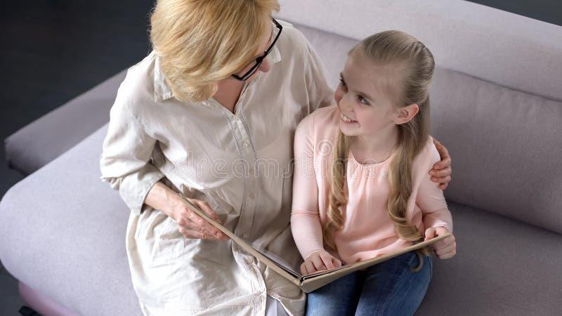 与她的年长保姆的微笑的小的女孩看书,关于孩子的关心 免版税库存图片