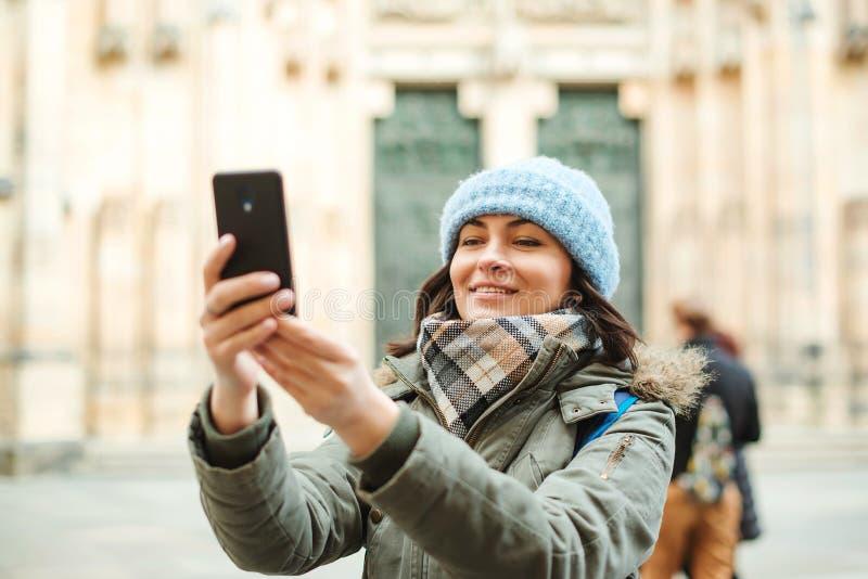 与她的电话的愉快的旅行妇女照相 秋天或冬天旅行 衣服暖和的年轻女人享受旅途的在欧洲 Peo 免版税图库摄影