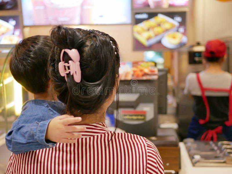 与她的看食物照片和读菜单的母亲一起的小亚裔婴孩在餐馆墙壁上决定什么到命令 免版税库存图片