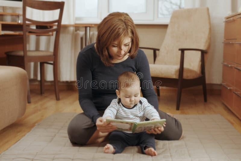 读与她的婴孩的母亲一本书 免版税库存图片