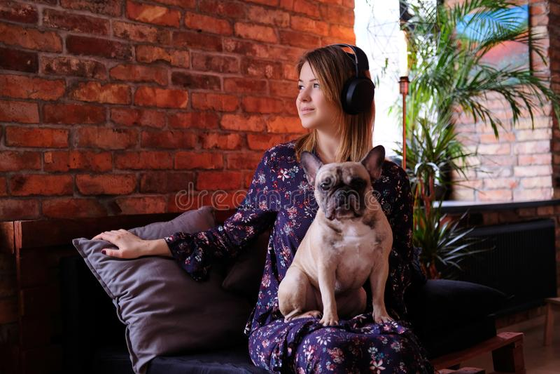 与她逗人喜爱的哈巴狗坐一个手工制造沙发和听到音乐的礼服的愉快的白肤金发的妇女在有顶楼的一间屋子里 免版税库存照片