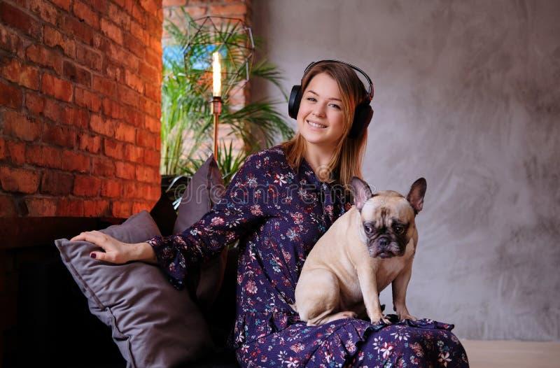 与她逗人喜爱的哈巴狗坐一个手工制造沙发和听到音乐的礼服的愉快的白肤金发的妇女在有顶楼的一间屋子里 免版税库存图片