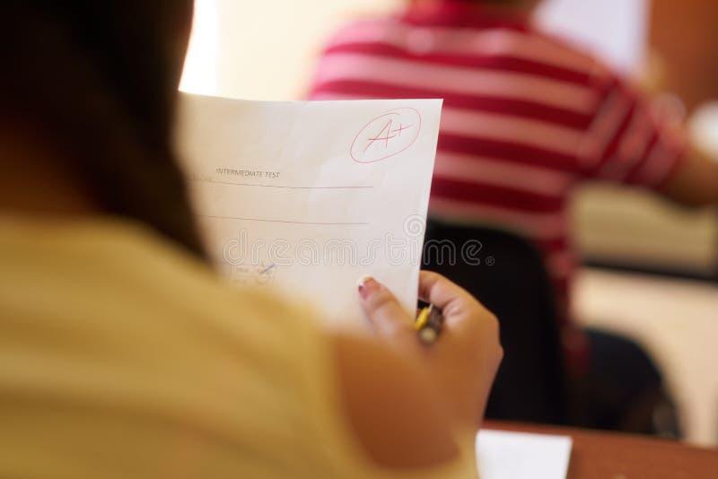 与好成绩的纸聪明的学生的在学校 库存图片