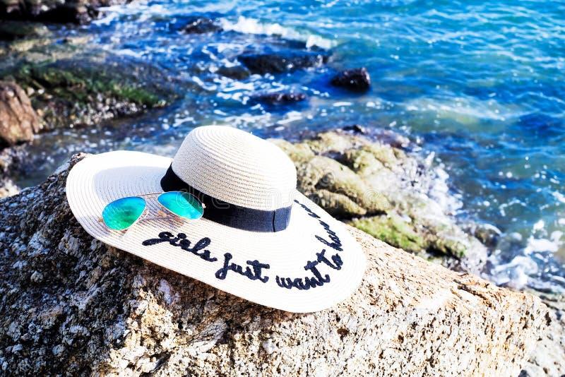 与妇女宽边缘帽子和太阳镜的海滩时尚 库存图片