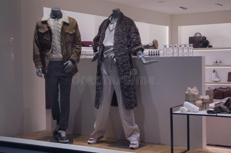 与妇女的和人的衣物的时装模特在一家奢侈品商店的窗口里 图库摄影
