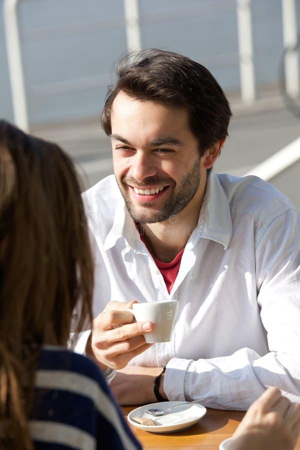 与妇女的愉快的年轻人饮用的咖啡 库存照片