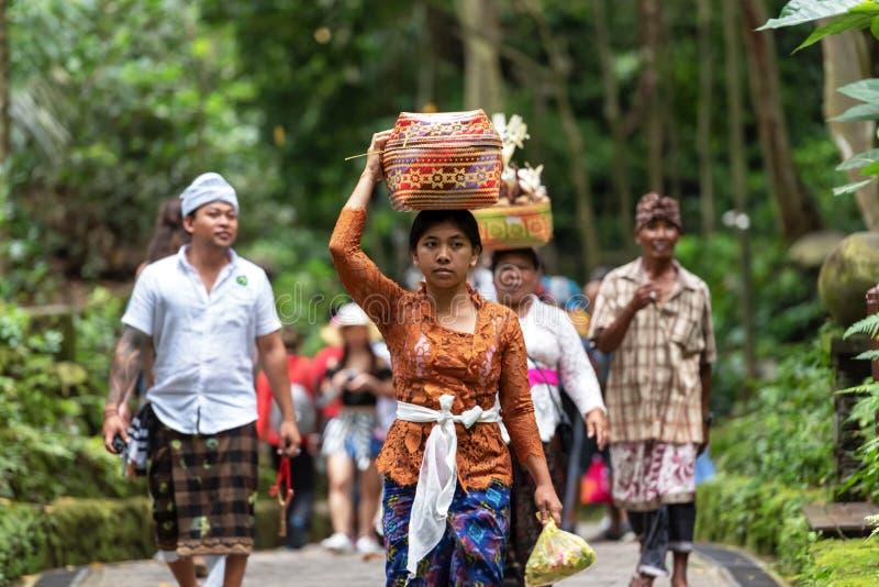 与妇女运载的提供的巴厘语游行Ubud猴子森林寺庙的印度上帝的 免版税图库摄影