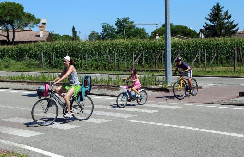 与妈妈的家庭和两个孩子穿过在crosswa的街道 图库摄影