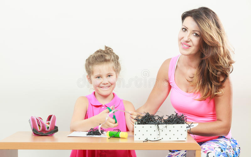 与妈妈的小女孩工作 免版税库存图片