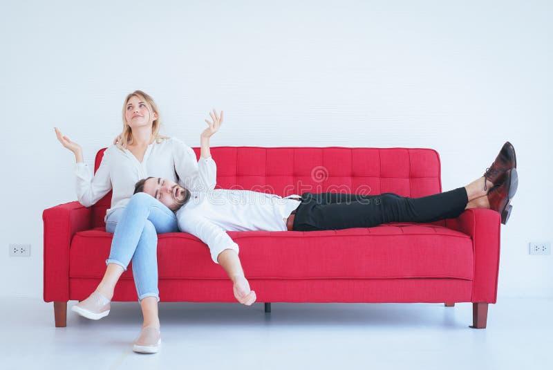 与妻子冲突和乏味的夫妇在房子的客厅,消极情感的丈夫打鼾 免版税图库摄影