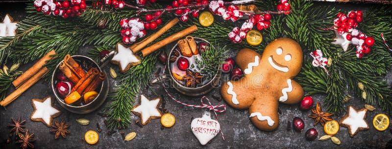 与姜饼人、杯子被仔细考虑的酒或拳打,冷杉分支、假日曲奇饼和欢乐装饰的圣诞节横幅 免版税库存照片