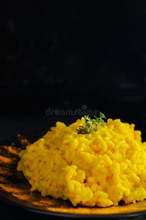 与姜黄的意大利煨饭在黑暗的背景 免版税库存照片