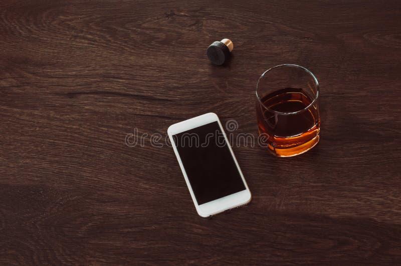 与威士忌酒、黄柏和手机谎言的玻璃在一张木桌上 免版税库存图片