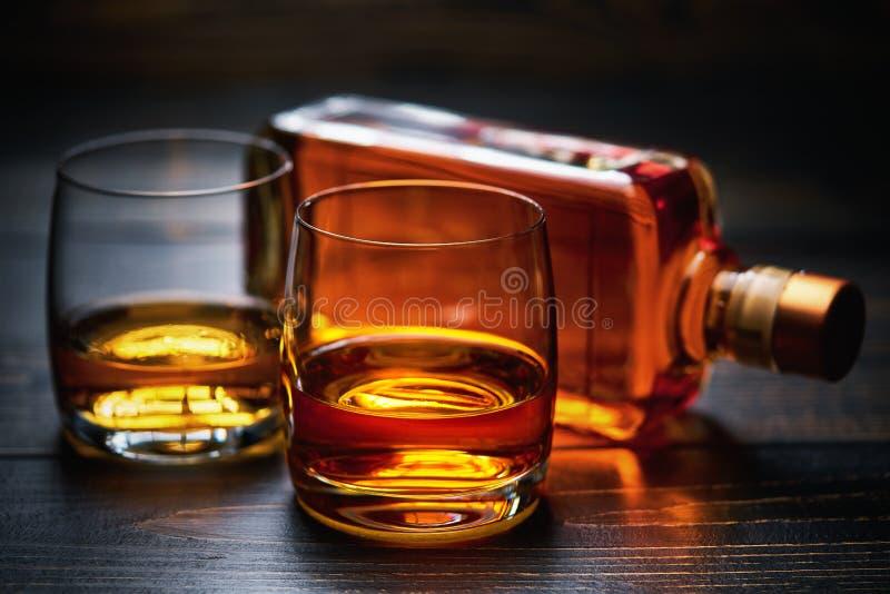 与威士忌酒和整瓶两射击的木桌  免版税库存照片