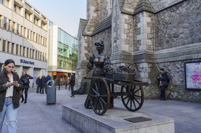 与娘娘腔的男人玛隆雕象的都伯林街市街道视图 免版税库存照片