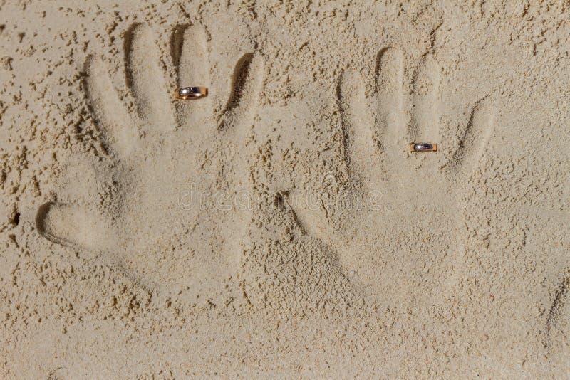 与婚戒的两个手印刷品在沙子靠岸,胜过 库存照片