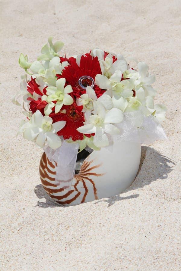 与婚戒的新娘花束在热带的沙子的壳是 免版税库存照片