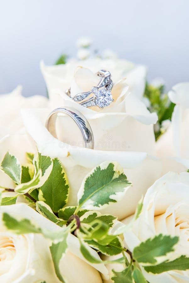 与婚礼乐队配对的定婚戒指,基于白玫瑰花束  免版税库存照片