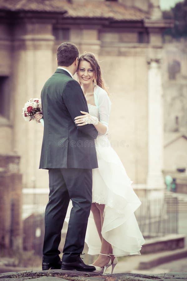 与婚礼礼服的已婚夫妇在城市 免版税库存图片
