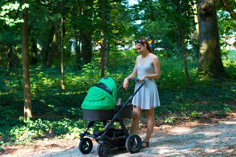 与婴儿推车,美丽的礼服的年轻母亲的自然步行走在有她的婴孩的森林走道的摇篮车的 免版税库存照片
